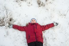Closeup of happy young boy lying on back in Winter Royalty Free Stock Photos