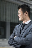 Closeup of a happy young Chinese business man looking away. Stock Photos