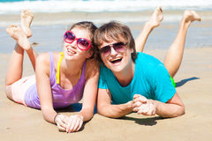 Closeup of happy young couple in sunglasses lying Royalty Free Stock Photos
