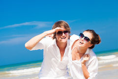 Closeup of happy young couple in white clothes. Having fun smiling on beach. This image has attached release Stock Photography