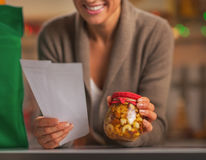 Closeup on happy young housewife with checks exploring christmas Stock Photo