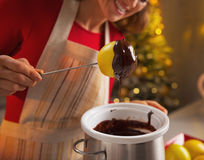 Closeup on happy young housewife making apple in chocolate glaze Stock Photos