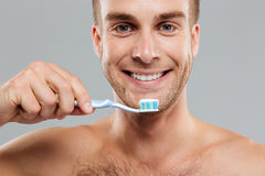 Closeup happy young man holding toothbrush with toothpaste Stock Image