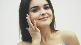 Closeup happy young woman applying cream to her face Skincare and cosmetics concept. Cosmetics. Woman face skin care. Closeup happy young woman applying cream to stock video footage