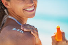 Closeup on happy young woman applying sun block creme Stock Photography