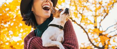 Closeup on happy young woman with dog outdoors in autumn lookin Royalty Free Stock Photography