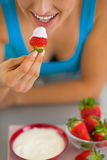 Closeup on happy young woman eating strawberry. With yogurt in kitchen Stock Photography