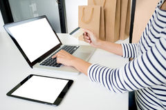 Closeup of happy young woman holding credit card inputting card. Information while and using laptop computer at home. Online shopping concept Stock Image