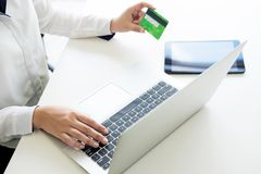 Closeup of happy young woman holding credit card inputting infor. Mation while and using laptop computer at home. Online shopping concept Stock Photography