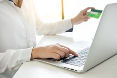Closeup of happy young woman holding credit card inputting infor. Mation while and using laptop computer at home. Online shopping concept Stock Image