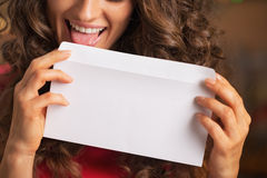 Closeup on happy young woman licking envelope royalty free stock photography
