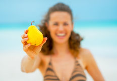 Closeup on happy young woman showing pear Royalty Free Stock Images