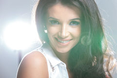 Closeup of a happy young woman smiling. With lights in her back Royalty Free Stock Images