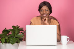 Closeup of happy young woman using laptop. Happy young African American woman with apple and cup Stock Image