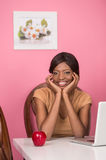 Closeup of happy young woman using laptop. Happy contented young African American woman with apple Stock Photos