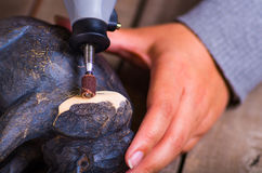 A closeup of a hardworker man using a polisher over a wood elephant on a wooden background Stock Images