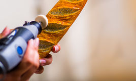 A closeup of a hardworker woman using a polisher over a wood brown piece Royalty Free Stock Image