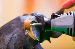 A closeup of a hardworker woman using a polisher over a wood elephant on a wooden background Stock Image