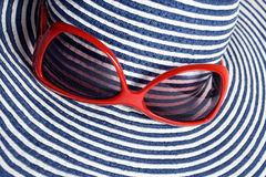 Closeup of hat and red sunglasses. Closeup of striped hat and red sunglasses Stock Photography