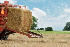 Closeup of a hay baler. Ready to drop bale with cloudy blue sky royalty free stock photography