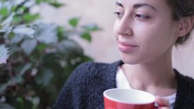 Closeup HD stock footage of woman with cup of coffee. Woman drinking coffee outdoors, enjoys the taste of the drink and. Inhales its flavor stock video