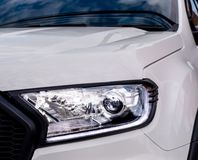 Closeup of a headlight on a modern car. White car stock image