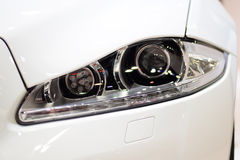 Closeup headlight of white car background Stock Photos