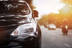 Closeup headlights of black car. Focusing on the black car headlights on a street corner with sunlight flares, In the background, the driver, bike and car stock photo