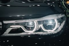 Closeup headlights of modern car during turn on light in night. Stock Photo