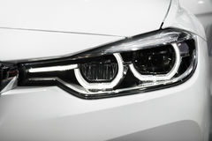 Closeup headlights of modern car during turn on light in night. Royalty Free Stock Photography