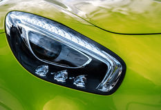 Closeup headlights of modern sport green car. Car exterior deta Stock Photo