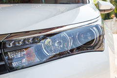 Closeup headlights of modern white car with LED daylight Stock Photos