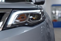Closeup headlights of a modern white color car. Detail on the front light of a car royalty free stock photos