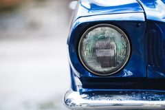Closeup headlights of retro muscle car. Car exterior detail.  Stock Photos