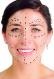 Closeup headshot caucasian woman with dotted lines drawn around face looking into camera, preparing cosmetic surgery Royalty Free Stock Photo