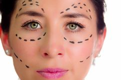 Closeup headshot caucasian woman with dotted lines drawn around face looking into camera, preparing cosmetic surgery Royalty Free Stock Photography