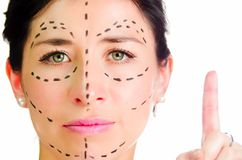 Closeup headshot caucasian woman with dotted lines drawn around face looking into camera, preparing cosmetic surgery Stock Photos