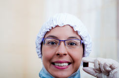 Closeup headshot female nurse wearing bouffant cap and glasses holding up two pill capsules for camera smiling Royalty Free Stock Images