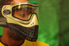 Closeup headshot man wearing green and black paintball protection facial mask covering entire face, transparent glass Royalty Free Stock Image