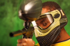 Closeup headshot man wearing green and black protection facial mask facing camera pointing paintball gun Stock Photo