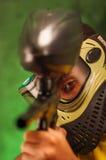 Closeup headshot man wearing green and black protection facial mask facing camera pointing paintball gun Royalty Free Stock Photo