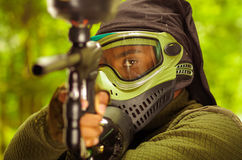 Closeup headshot man wearing green and black protection facial mask facing camera pointing paintball gun Stock Photos