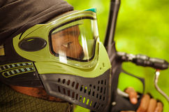 Closeup headshot man wearing green and black protection facial mask standing in profile angle, forest background Royalty Free Stock Photos