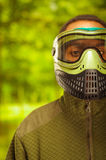Closeup headshot man wearing jacket, green and black protection facial mask standing facing camera, forest background Royalty Free Stock Photo