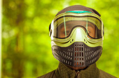 Closeup headshot man wearing jacket, green and black protection facial mask standing facing camera, forest background Royalty Free Stock Image
