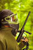 Closeup headshot man wearing jacket, green and black protection facial mask standing in profile angle with weapon Stock Photo