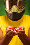 Closeup headshot man wearing yellow shirt, green and black protection facial mask holding up pile of paintball. Ammunition royalty free stock photography