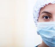 Closeup headshot nurse wearing bouffant cap and facial mask, half of head visible, one eye staring into camera Stock Photos