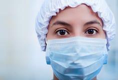 Closeup headshot nurse wearing bouffant cap and facial mask staring into camera with beautiful dark eyes Stock Photos
