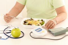 Closeup of healthy diet. Elderly woman eating healthy diet, salad and apple Stock Photo